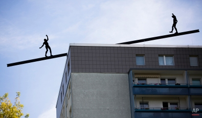 Two aluminum figures of an installation are silhouetted on a rooftop in Berlin, Germany, July 24, 2013. (AP Photo/Gero Breloer)