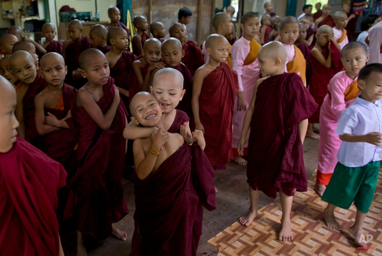 A novice Buddhist monk playfully holds another, as other novice monks, nuns and children gather for an assembly at the beginning of a school day at a monastic school in Yangon, Myanmar, June 12, 2015. (AP Photo/Gemunu Amarasinghe)