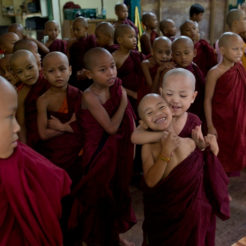 A novice Buddhist monk playfully holds another, as other novice monks, nuns and children gather for an assembly at the beginning of a school day at a monastic school in Yangon, Myanmar, Friday, June 12, 2015. Monastic schools, founded and run by the monks with a little support from the government, provide education for over 150,000 children. (AP Photo/Gemunu Amarasinghe)