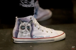 In this Saturday, June 6, 2015 photo, Karen Pennington wears a pair of custom-printed shoes while shopping at the first-ever CatConLA in Los Angeles. (AP Photo/Jae C. Hong)
