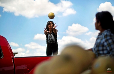 Ailyn Lopez, 13, catches a melon tossed to her by her sister Jocelyn Lopez, 14, right, as they load up a customer's pickup truck while helping out at their parent's farm stand, June 5, 2015, in Atlanta. (AP Photo/David Goldman)