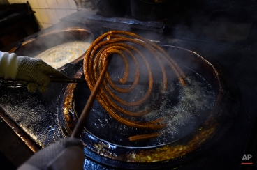 A ''Churro'' is prepared to serve in the old kitchen of an ancient ''Churreria'' store, where ''Churros'', a typical breakfast food, are prepared, in Pamplona northern Spain, June 27, 2015. (AP Photo/Alvaro Barrientos)