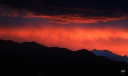 Clouds are illuminated as the sun sets behind the mountains, June 13, 2015, in Denver. (AP Photo/David Zalubowski)