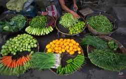 A vegetable seller sprays water on vegetables to keep them fresh at a market in Gauhati, India, Monday, June 8, 2015. (AP Photo/ Anupam Nath)