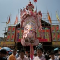 """A girl dressed in a traditional Chinese costume """"floats"""" in the air, supported by a rig of hidden metal rods, during a parade on the outlying Cheung Chau island in Hong Kong Monday, May 25, 2015, to celebrate the Bun Festival. The festival is held every year to placate the spirits of people killed by pirates. (AP Photo/Vincent Yu)"""