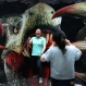 A Chinese girl shares a light moment with her friend as she poses with a 3D painting showing a dinosaur at an art exhibition at a shopping mall in Beijing, China, Wednesday, May 13, 2015. Shopping malls in the capital city often organize events in their mall to attract customers and a change to boost their sales. (AP Photo/Andy Wong)