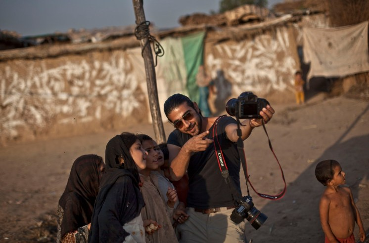 Photographer Muhammed Muheisen shows Afghan refugee children how the camera works, in a poor neighborhood on the outskirts of Islamabad, Pakistan, Oct. 21, 2013. (AP Photo/Nathalie Bardou)
