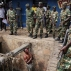 Jean Claude Niyonzima, a suspected member of the ruling party's Imbonerakure youth militia, pleads with soldiers to protect him from a mob of demonstrators after he came out of hiding in a sewer in the Cibitoke district of Bujumbura, Burundi, Thursday, May 7, 2015. Niyonzima fled from his house into the sewer under a hail of stones thrown by a mob protesting President Pierre Nkurunziza's decision to seek a third term in office. At least one protestor has died in clashed with the widely feared Imbonerakure militias and police, sending scores to the streets seeking revenge. (AP Photo/Jerome Delay)