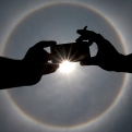 A man uses his mobile phone to photograph a circular sun halo in Mexico City, Thursday, May 21, 2015. The ring around the sun is a fairly common weather phenomenon caused by ice crystals in the upper atmosphere. (AP Photo/Marco Ugarte)