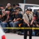 A McLennan County deputy stands guard near a group of bikers in the parking lot of a Twin Peaks restaurant Sunday, May 17, 2015, in Waco, Texas. (Rod Aydelotte/Waco Tribune-Herald via AP)