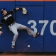 Miami Marlins left fielder Christian Yelich hits the wall while trying to catch a ball hit by New York Mets' Curtis Granderson during the fourth inning of a baseball game Saturday, May 30, 2015, in New York. (AP Photo/Frank Franklin II)