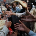 A Pakistani man distributes bread to poor people during a month of Ramadan in Peshawar, Pakistan, Thursday, June 18, 2015. Muslims throughout the world are marking Ramadan - a month of fasting during which the observants abstain from food, drink and other pleasures from sunrise to sunset. Ramadan is meant to be a time of reflection and worship, remembering the hardships of others and being charitable. (AP Photo/Mohammad Sajjad)