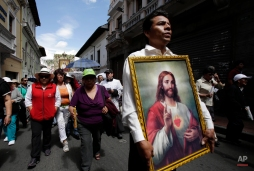In this June 14, 2015 photo, a man parades with a framed image of the Sacred Heart of Jesus during a procession marking Ecuador's identity as a Catholic nation with its consecration to the Sacred Heart of Jesus in 1874, in Quito. Although eight of 10 people in Ecuador say they are Catholic, many take part in festivals that feature joyous dances and ceremonial acts of thanks to the ancient native gods. (AP Photo/Dolores Ochoa)