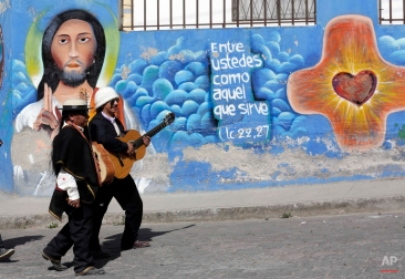 In this June 24, 2015 photo, two musicians walk past a religious mural in Peguche, Ecuador, during the celebrations of the Catholic feast day for St. John the Baptist and the Indian celebration Inti Raymi or Festival of the Sun. (AP Photo/Dolores Ochoa)