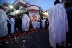 In this June 4, 2015 photo, after the indigenous dancers are long gone, Catholic priests take part in a procession through the streets of PujilÌ, Ecuador, continuing with the the Catholic ritual of the Corpus Christi festivities. (AP Photo/Dolores Ochoa)