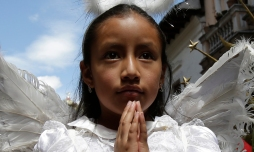 In this June 14, 2015 photo, a girl dressed as angel parades with her hands folded in prayer during a procession marking Ecuador's identity as a Catholic nation with its 1874 consecration to the Sacred Heart of Jesus, in Quito. (AP Photo/Dolores Ochoa)