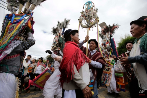 In this June 7, 2015 photo, the steward or prioste, accompanied by his family, leads the way for the dancers during the Corpus Christi celebrations Danzante de PujilÌ, in Pujili, Ecuador. Dressed in brightly colored costumes and tall headdresses decorated with beads, coins, crosses and mirrors, the performers danced to the indigenous deities. (AP Photo/Dolores Ochoa)