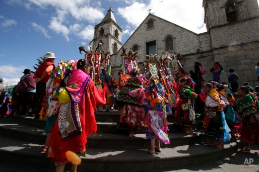 In this June 4, 2015 photo, a group of dancers enter the church, beginning the start of the Corpus Christi festival, in Pujili, Ecuador. (AP Photo/Dolores Ochoa)