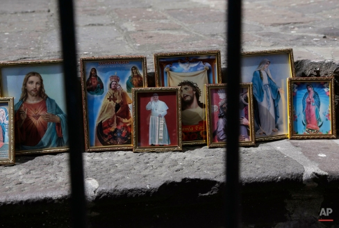 This June 14, 2015 photo shows framed images of Catholic icons on a street in downtown Quito, Ecuador. (AP Photo/Dolores Ochoa)