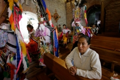 In this June 4, 2015 photo, a group of dancers enter the church, marking the start of the Corpus Christi festival, in Pujili, Ecuador. The priest authorizes the entry of the dancers who then perform dancers in honor of the Christian God. (AP Photo/Dolores Ochoa)
