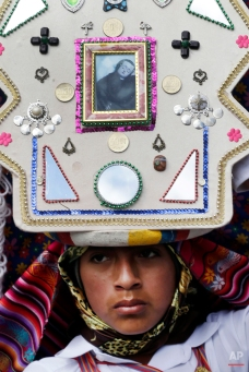 In this June 4, 2015 photo, a Pujili dancer wears a headdress decorated with Catholic and indigenous symbols, as he performs in the streets of Pujili, Ecuador, during the Corpus Christi celebrations, jointly honoring the Holy Communion, or Eucharist, and Inti, the ancient Inca sun god. (AP Photo/Dolores Ochoa)
