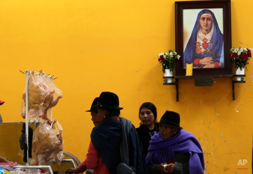 In this June 7, 2015 photo, women walk past an altar dedicated to Our Lady of Sorrows, as they enter a market in Pujili, Ecuador. Pope Francis will encounter rich indigenous traditions on his South America trip that date back centuries to even before European priests brought Christianity to the New World. (AP Photo/Dolores Ochoa)