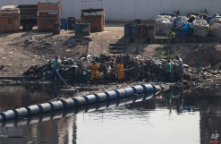 In this July 28, 2015 photo, workers remove garbage collected by floating waste barriers in a canal at the Mare slum complex, in Rio de Janeiro, Brazil. Rio's historic sewage problem spiraled over the past decade as the population exploded with many of the metropolitan area's 12 million residents settling in the vast slums that ring the bay. Waste flows into over 50 streams that empty into the once-crystalline Guanabara Bay. (AP Photo/Silvia Izquierdo)