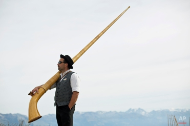 An alpenhorn player carries his instrument near the Lac de Tracouet, situated 2200 meters (7220 feet) above sea level in Haute-Nendaz, canton of Valais, Switzerland, Sunday, July 26, 2015. (AP Photo/David Azia)