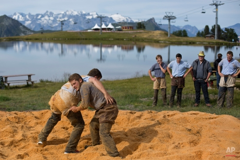 Men perform Schwingen, traditional Swiss wrestling, along the Lac de Tracouet, situated 2200 meters (7220 feet) above sea level in Haute-Nendaz, canton of Valais, Switzerland, Sunday, July 26, 2015. (AP Photo/David Azia)