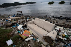 In this June 1, 2015 photo, a discarded sofa litters the shore of Guanabara Bay in Rio de Janeiro, Brazil. As part of its Olympic bid, Brazil promised to build eight treatment facilities to filter out much of the sewage and prevent tons of household trash from flowing into the Guanabara Bay. Only one has been built. Tons of household trash line the coastline and form islands of refuse. (AP Photo/Silvia Izquierdo)
