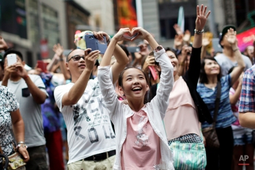 Visitors to Times Square react as they see images of themselves on a jumbotron, July 30, 2015, in New York. (AP Photo/Mary Altaffer)