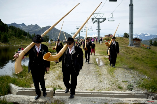 Alpenhorn players from the French Haute Savoie region walk along the Lac de Tracouet, situated 2200 meters (7220 feet) above sea level in Haute-Nendaz, canton of Valais, Switzerland, Sunday, July 26, 2015. More than 200 alpenhorn players gathered in Nendaz on Sunday to perform as an ensemble in the Alpenhorn Festival. (AP Photo/David Azia)