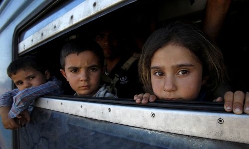 In this photo taken on Thursday, July 23, 2015 children, migrants from Afghanistan, look through a window after boarding a train to Serbia with their parents, at the railway station in the southern Macedonian town of Gevgelija. Macedonia is facing an increasing pressure of migrants flow on its southern and northern borders with Greece and Serbia. (AP Photo/Boris Grdanoski)