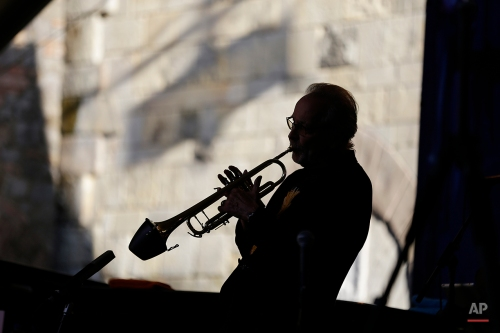 In this photo taken July 23, 2015, trumpeter Herb Alpert is silhouetted performing in the courtyard of the Castello di Amorosa winery in Calistoga, Calif. The performance was part of the Napa Valley Festival del Sole, a 10-day summer festival of music, theater and dance with the region's wine and cuisine. Alpert, 80, is a nine-time Grammy award winner and National Medal of Arts recipient. (AP Photo/Eric Risberg)