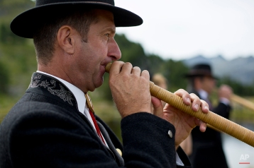 An alpenhorn player from the French Haute Savoie region performs along the Lac de Tracouet, situated 2200 meters (7220 feet) above sea level in Haute-Nendaz, canton of Valais, Switzerland, Sunday, July 26, 2015. (AP Photo/David Azia)