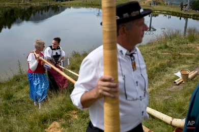 Alpenhorn players chat amongst themselves along the Lac de Tracouet, situated 2200 meters (7220 feet) above sea level in Haute-Nendaz, canton of Valais, Switzerland, Sunday, July 26, 2015. (AP Photo/David Azia)