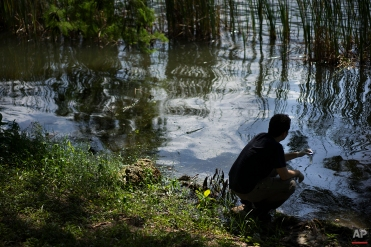 """In this April 28, 2015 photo, Fernando Spilki, the head of the environmental studies program at Feevale University, takes water samples from the Rodrigo de Freitas Lake, in Rio de Janeiro, Brazil. With little to no sewage treatment, Spilki said, """"the quantity of fecal matter entering the waterbodies in Brazil is extremely high. Unfortunately, we have levels comparable to some African nations, to India."""" (AP Photo/Felipe Dana)"""