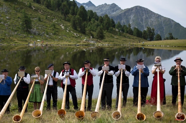 Alpenhorn players perform along the Lac de Tracouet, situated 2200 meters (7220 feet) above sea level in Haute-Nendaz, canton of Valais, Switzerland, Sunday, July 26, 2015. (AP Photo/David Azia)