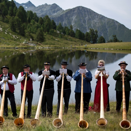 Alpenhorn players perform along the Lac de Tracouet, situated 2200 meters (7220 feet) above sea level in Haute-Nendaz, canton of Valais, Switzerland, Sunday, July 26, 2015. More than 200 alpenhorn players gathered in Nendaz on Sunday to perform as an ensemble in the Alpenhorn Festival. (AP Photo/David Azia)
