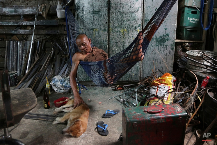 "Filipino Victor San Miguel pats his dog named ""Polgoso"" as he takes a break after working the night shift at their tire repair shop in Manila, Philippines, July 21, 2015. (AP Photo/Aaron Favila)"