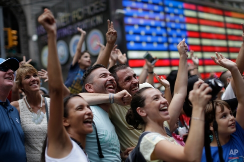 Visitors in Times Square react as they see images of themselves on a large screen in New York. (AP Photo/Mary Altaffer)