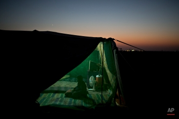 A Syrian refugee prays inside her tent at an informal settlement near the Syrian border on the outskirts of Mafraq, Jordan, July 25, 2015. (AP Photo/Muhammed Muheisen)