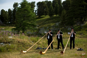 Alpenhorn players practice near the Lac de Tracouet, situated 2200 meters (7220 feet) above sea level in Haute-Nendaz, canton of Valais, Switzerland, Sunday, July 26, 2015. (AP Photo/David Azia)