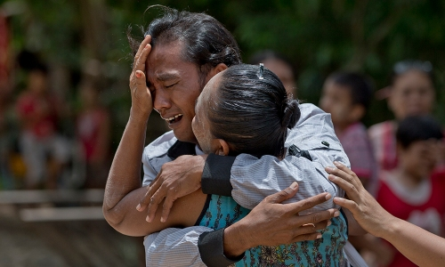 In this May 16, 2015 photo, former slave fisherman Myint Naing, left and his mother Khin Than, cry as they are reunited after 22 years at their village in Mon State, Myanmar. Myint, 40, is among hundreds of former slave fishermen who returned to Myanmar following an Associated Press investigation into the use of forced labor in Southeast Asia's seafood industry. (AP Photo/Gemunu Amarasinghe)