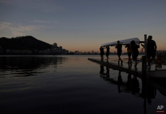 In this July 13, 2015 photo, men carry a rowing boat for a practice session in the Rodrigo de Freitas Lake, in Rio de Janeiro, Brazil. The lake, which was largely cleaned up in recent years, was thought be safe for rowers and canoers. Yet Associated Press tests found its waters to be among the most polluted for Olympic sites. (AP Photo/Leo Correa)