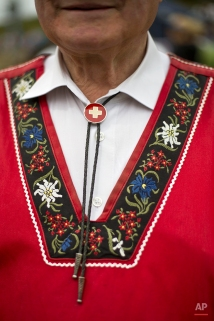An alpenhorn player wearing a traditional Swiss tunic poses for a photograph along the Lac de Tracouet, situated 2200 meters (7220 feet) above sea level in Haute-Nendaz, canton of Valais, Switzerland, Sunday, July 26, 2015. (AP Photo/David Azia)