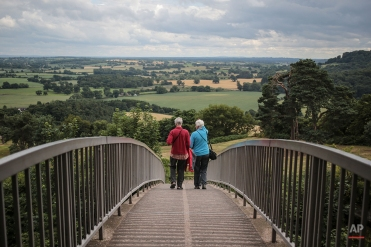 A couple walk across a bridge crossing to Beeston Castle, a former Royal Castle situated over 100m above ground level, in Cheshire, northern England, July 22, 2015. (AP Photo/Mosa'ab Elshamy)