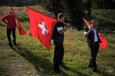 Men carry Swiss flags near the Lac de Tracouet, situated 2200 meters (7220 feet) above sea level in Haute-Nendaz, canton of Valais, Switzerland, Sunday, July 26, 2015. (AP Photo/David Azia)