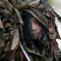 A muddied girl, donning a cape made of dried banana leaves, collects candles before attending a mass to celebrate the Feast Day of St. John the Baptist in the village of Bibiclat, Aliaga township, Nueva Ecija province in northern Philippines,Wednesday, June 24, 2015. (AP Photo/Bullit Marquez)