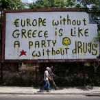 """Two men walk under a graffiti on a disused billboard by street artist Cacao Rocks in Athens, on Tuesday, June 16, 2015. Greece insisted Monday it is ready to return to bailout talks """"at any moment"""" after a breakdown in negotiations with creditors pushed the country closer toward bankruptcy and jolted international markets. (AP Photo/Petros Giannakouris)"""